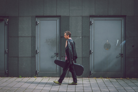 guitar case: Man in short sleeve shirt walking in the street with guitar case