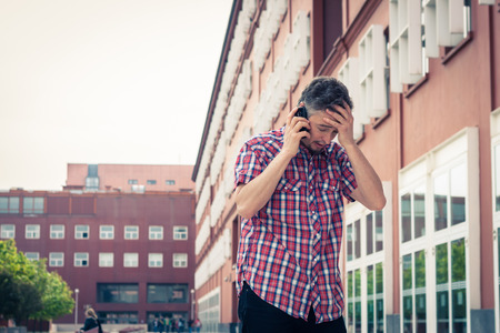 Man in short sleeve shirt talking on phone in the street Stock Photo