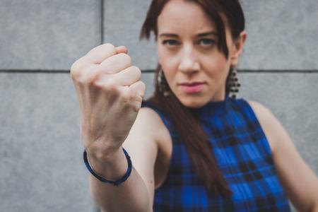 menacing: Menacing pretty girl showing her fist  Stock Photo
