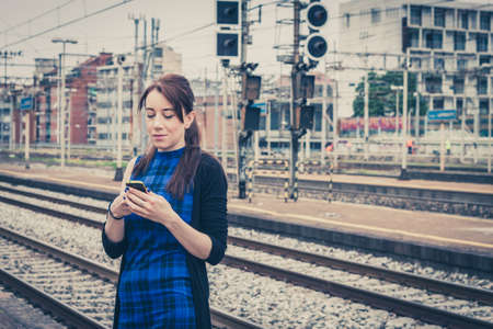 Pretty girl texting on phone along the tracks in a railroad station photo