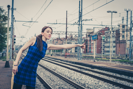 Pretty girl hitchhiking along the tracks in a railroad station photo