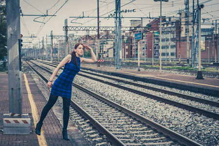 Pretty girl posing along the tracks in a railroad station photo