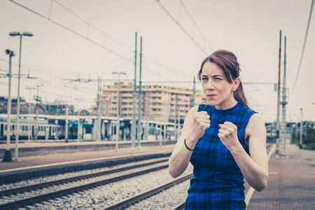 Pretty girl ready to fight along the tracks in a railroad station photo