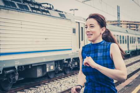 Pretty girl running along the tracks in a railroad station photo