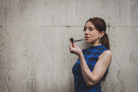 Pretty girl smoking vintage pipe in the street photo