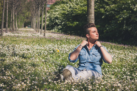 Short hair girl sitting in the grass with flowers photo