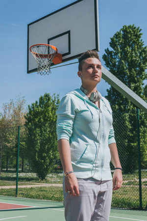 Short hair girl with hoodie in a basketball playground photo