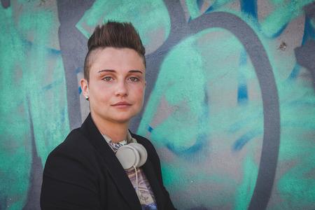 Piuttosto breve ragazza capelli con il nero posa giacca contro un muro