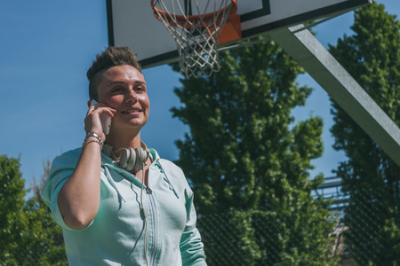 Short hair girl with hoodie talking on phone in a basketball playground photo