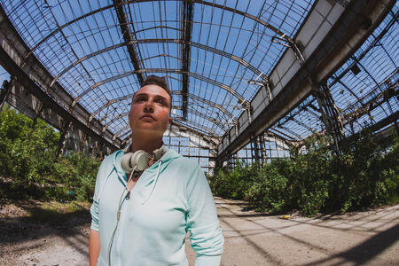 Fisheye portrait of short hair girl with hoodie posing in an abandoned factory photo