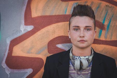 lesbienne: Jolie jeune fille aux cheveux court avec la veste noire posant contre un mur