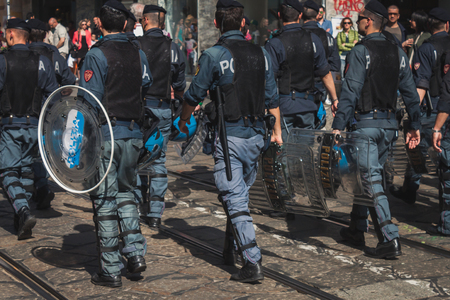 demonstrators: MILAN, ITALY - MAY 1: Policemen follow Mayday parade where people celebrate the international Workers Day on MAY 1, 2014 in Milan.