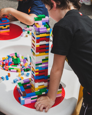 MILAN, ITALY - MAY 10: Children play at Lego Village, event held in the city streets to promote creativity and manual ability on MAY 10, 2014 in Milan. Editoriali