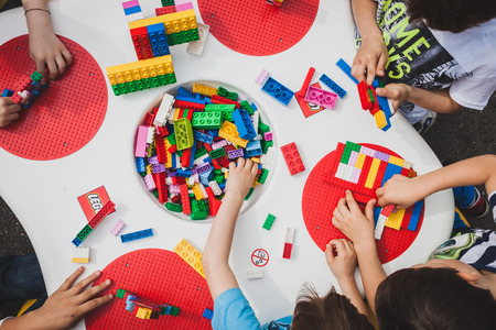 MILAN, ITALY - MAY 10: Children play at Lego Village, event held in the city streets to promote creativity and manual ability on MAY 10, 2014 in Milan. Редакционное