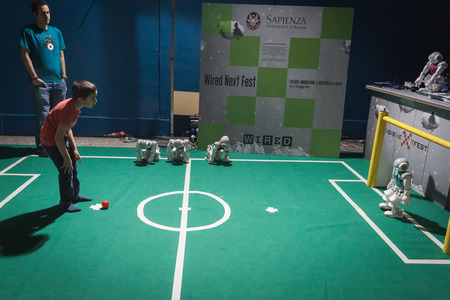 MILAN, ITALY - MAY 17: Kid plays soccer with Nao robot at Wired Next Fest, event dedicated to future, innovation and creativity on MAY 17, 2014 in Milan.