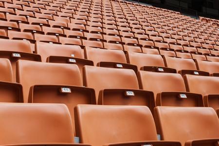 aloneness: Perspective of many empty orange stadium seats
