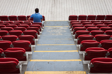aloneness: Empty red stadium seats with a man alone