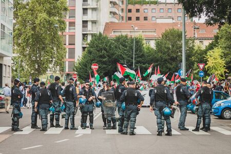 MILAN, ITALY - JULY 26: Riot police follows people marching and protesting against Gaza strip bombing in solidarity with Palestinians on JULY 26, 2014 in Milan.