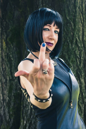 Pretty dark goth girl posing in a city park photo
