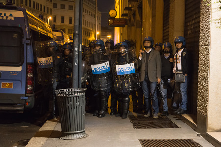 demonstrators: MILAN, ITALY - OCTOBER 11: Policemen beside the Turkish consulate watch demonstrators protesting and asking help for Kurdish people in Syria on OCTOBER 11, 2014 in Milan. Editorial