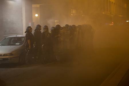 demonstrators: MILAN, ITALY - OCTOBER 11: Demonstrators launch smoke canisters to police in front of the Turkish consulate while asking help for Kurdish people in Syria on OCTOBER 11, 2014 in Milan. Editorial