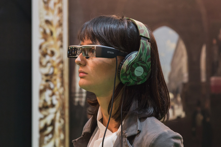 MILAN, ITALY - OCTOBER 22: Woman wearing glasses for augmented reality at Smau, international exhibition of information communications technology on OCTOBER 22, 2014 in Milan.