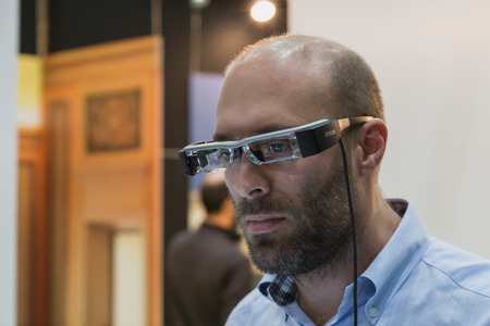 MILAN, ITALY - OCTOBER 22: Man wearing glasses for augmented reality at Smau, international exhibition of information communications technology on OCTOBER 22, 2014 in Milan. Editoriali