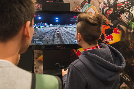 gamers: MILAN, ITALY - OCTOBER 24: People play at Games Week 2014, event dedicated to video games and electronic entertainment on OCTOBER 24, 2014 in Milan. Editorial