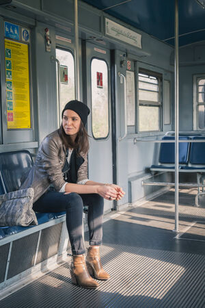 Pretty girl with beanie posing in a metro car photo