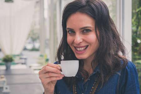 jolie fille: Jolie fille avec de longs cheveux en buvant une tasse de caf� Banque d'images