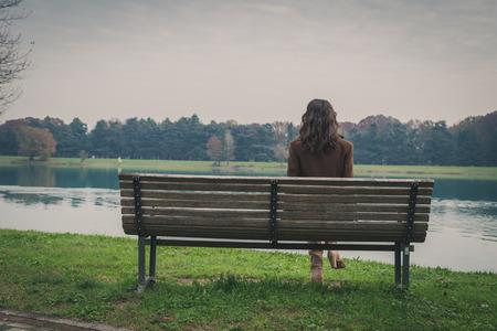 soledad: Joven y bella mujer con el pelo largo que se sienta en un banco en un parque de la ciudad Foto de archivo