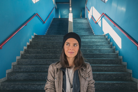 Pretty girl with beanie posing in a metro station Stock Photo