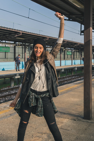 dancing girl: Pretty girl with beanie listening to music in a metro station Stock Photo