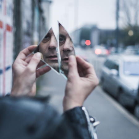 mirror image: Punk guy looking at himself in a shattered mirror in the city streets Stock Photo