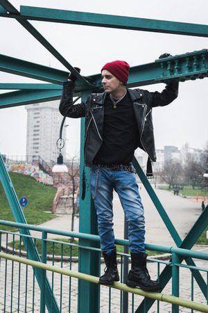 clothes interesting: Punk guy with beanie standing on a bridge