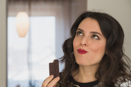 Beautiful young brunette with long hair eating chocolate at home