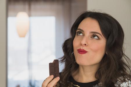 Joven y bella morena con el pelo largo comer chocolate en casa Foto de archivo - 34654684