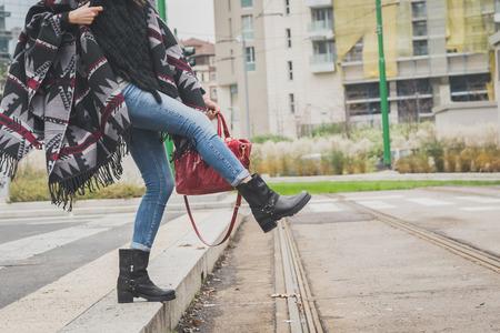 modelos posando: Detalle de una mujer joven con la presentaci�n del poncho en las calles de la ciudad