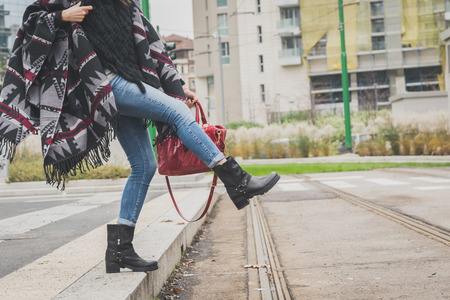 Particolare di una giovane donna con poncho in posa per le strade della città