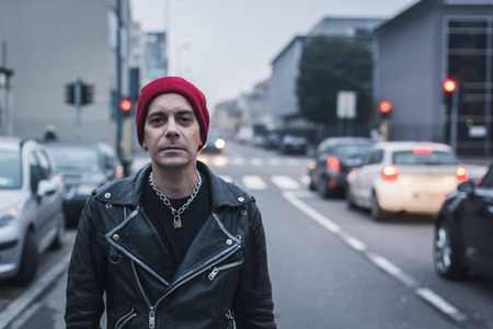 clothes interesting: Punk guy with beanie posing in the city streets Stock Photo