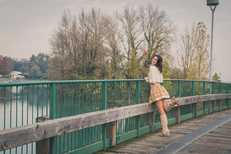 Beautiful young woman with long hair posing on a bridge