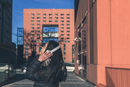 escuchando musica: Niña china hermosa joven con los auriculares escuchando música en las calles de la ciudad