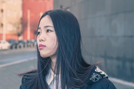 mujer pensativa: Ni�a china hermosa joven con el pelo largo que presenta en las calles de la ciudad
