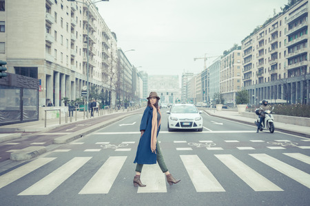 crossing street: Beautiful young brunette with hat posing in the city streets Stock Photo