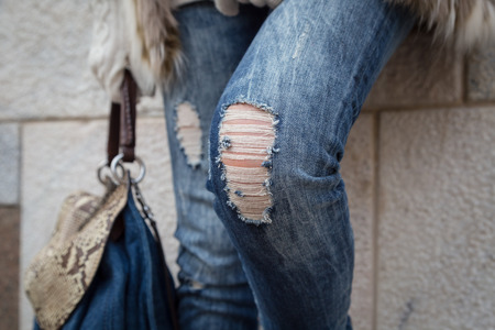 ripped jeans: Detail of a young woman with bag posing in the city streets