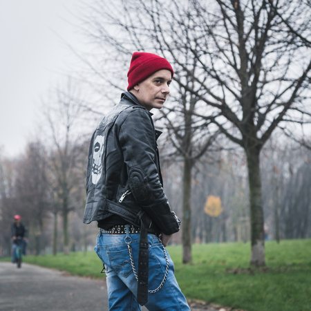 Punk guy with beanie posing in a city park