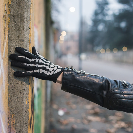 Detail of a punk guy with gloves posing in the city streets photo