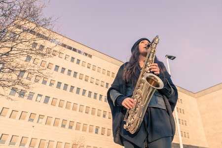 tenor: Beautiful young woman playing tenor saxophone in the city streets