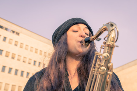 the tenor: Beautiful young woman playing tenor saxophone in the city streets