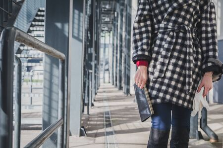 Particolare di una giovane donna con frizione che propone il sacchetto nelle vie della città